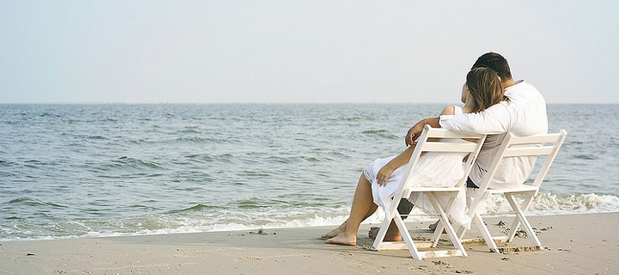 couple sitting on the beach in all white