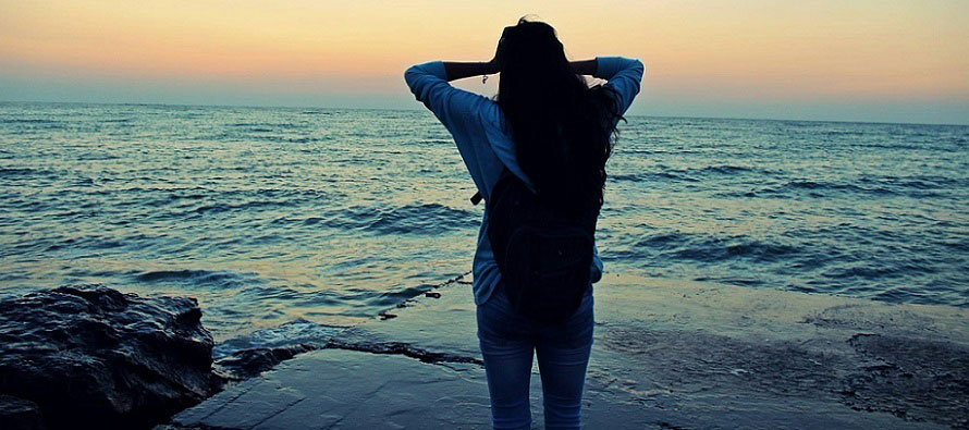 girl holding her head looking at sunset