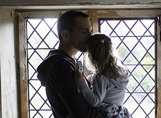father kisses daughter by window