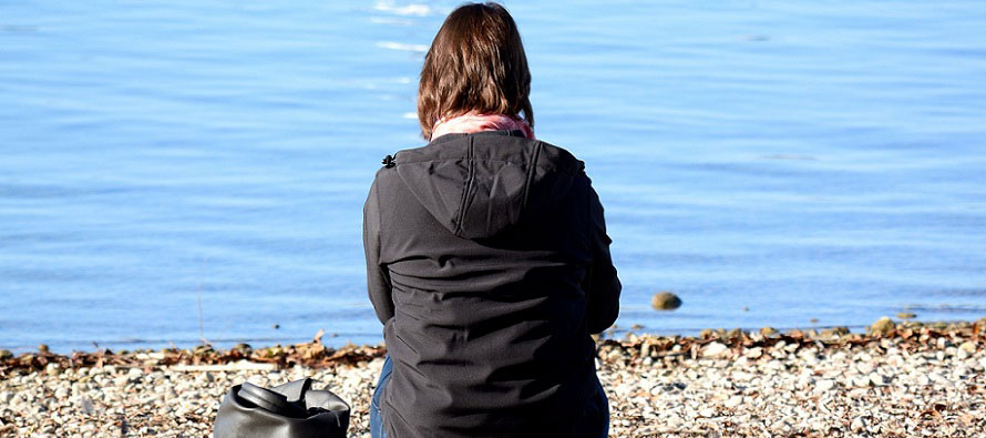 woman sitting alone near shore