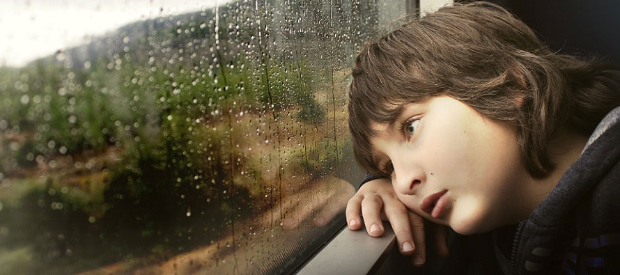 sad child leaning on window