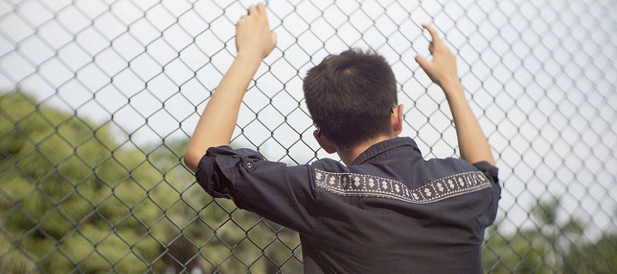 teen holding onto fence