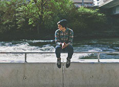 teen sitting on a bridge over water