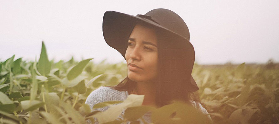 woman in a field wearing a hat